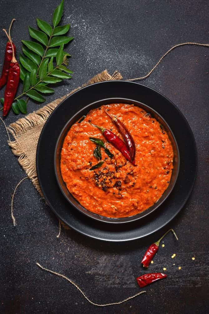 Kerala Style red coconut chutney on black plate with some red chilies and curry leaves spread around.