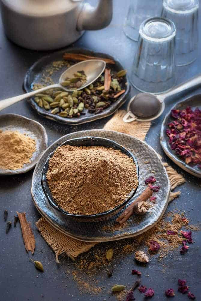 Chai masala powder in black bowl with some spice and rose petals spread around, glasses and teapot at the back.