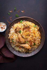 Overhead shot of chicken biryani served on copper plate with yogurt raita on the side.
