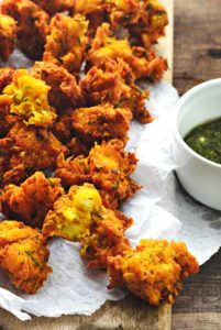 Close up shot of corn paneer pakoda on butter paper placed on wooden platter.