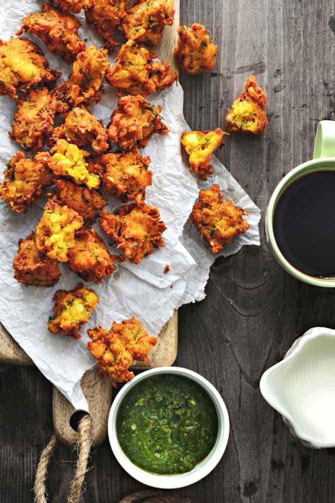 Corn paneer pakoda on butter paper over the wooden board, chutney and tea on the side.