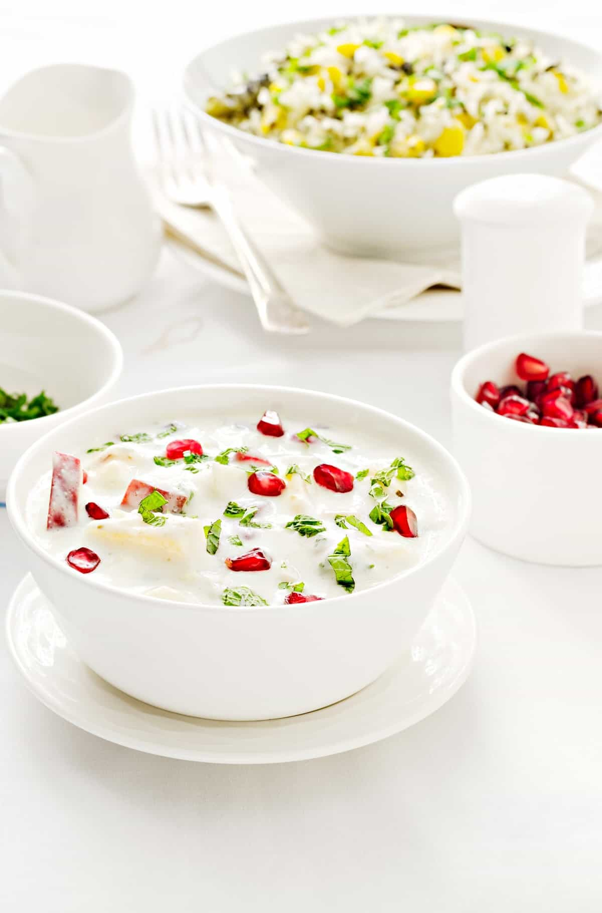 Mix Fruit Raita served in white bowl, rice pilaf and pomegranate in bowl at the back.