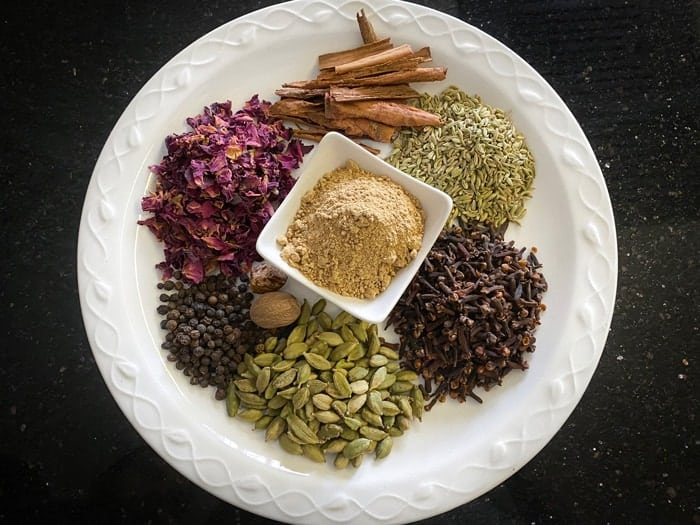 Chai masala ingredients on white plate.