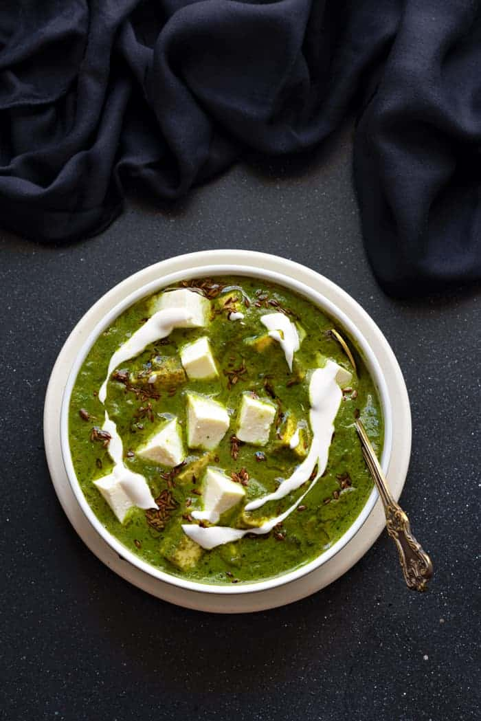 Palak paneer in a white bowl, with a spoon into it.