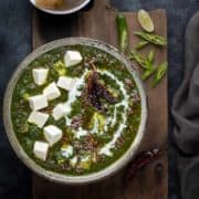 Restaurant style palak paneer curry in grey ceramic bowl, naan bread on the side.