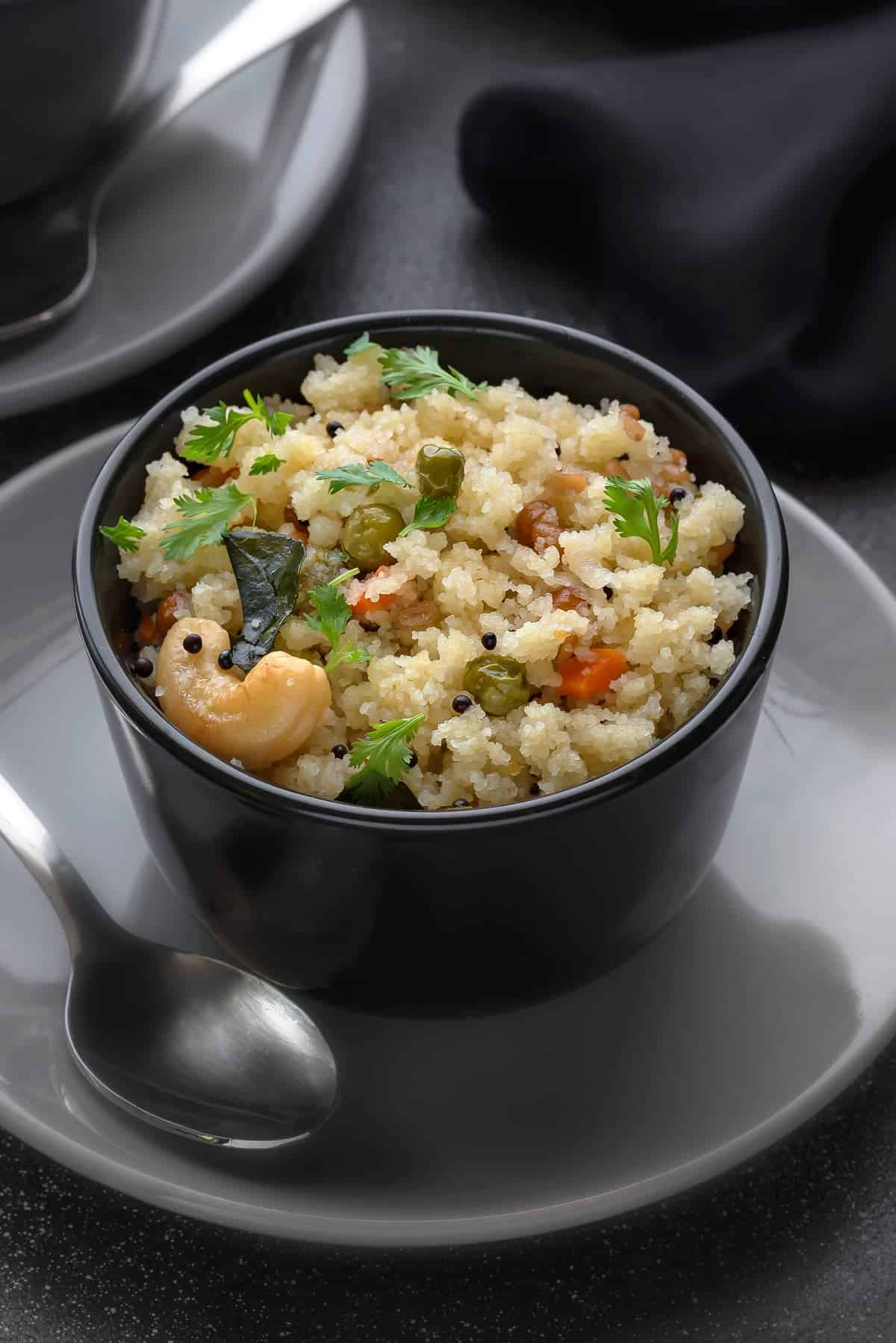 South Indian rava upma dish served in black bowl, with a spoon on side.