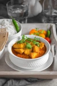 Close up shot of yam curry or Suran ki sabji in white bowl placed on wooden tray, roti and rice on the side.