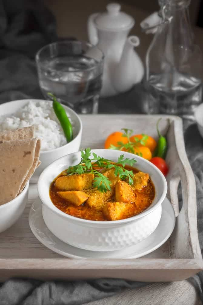 Yam curry or Suran sabzi in white bowl placed on wooden tray, roti and rice on the side.