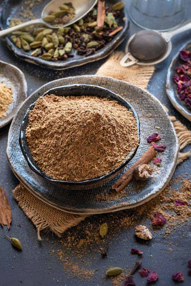 Close up shot of Indian chai masala or tea masala in black bowl with spices and rose petals spread around.