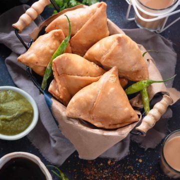 Overhead shot of flaky Indian aloo samosa in basket, tea and chutney on the side.