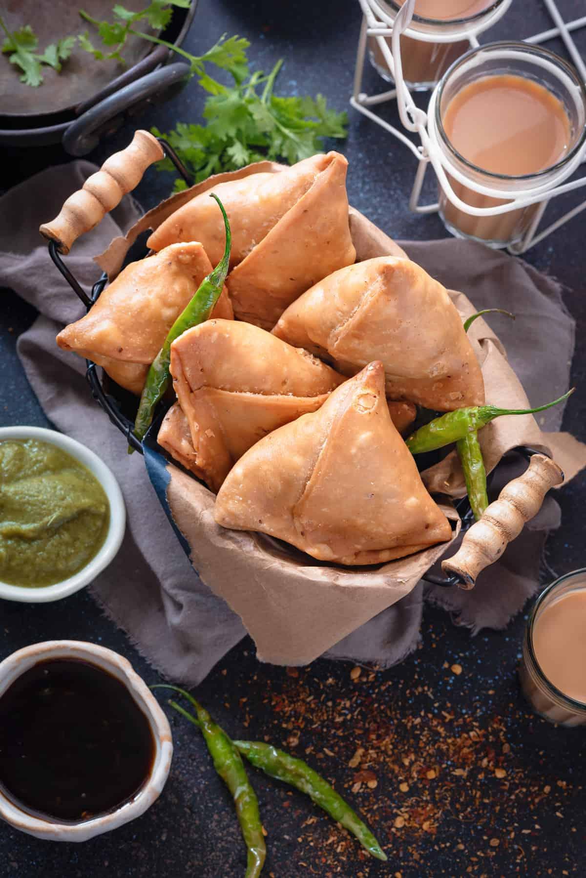 Overhead shot of flaky Indian Punjabi samosa in basket, tea and chutney on the side.
