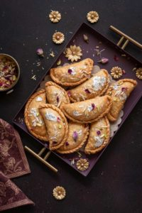 Overhead shot of flaky mawa gujiya sweet served in purple metal tray.