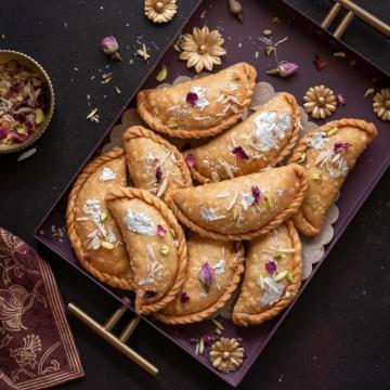 Overhead shot of flaky mawa gujiya sweet served in purple metal tray.