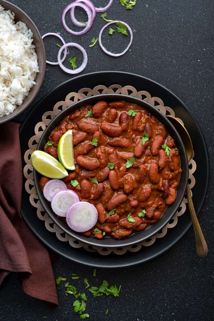 Rajma masala curry served in black plate, with a bowl of rice on side.