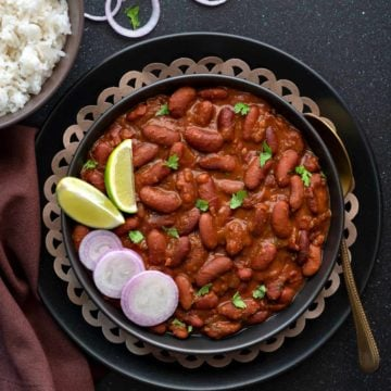 Punjabi Rajma masala served in black plate with a spoon into it.