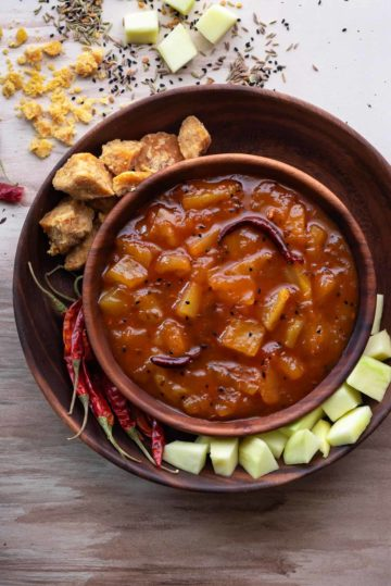Aam ki launji in wooden bowl with jaggery, red chillies and raw mangoes spread around.