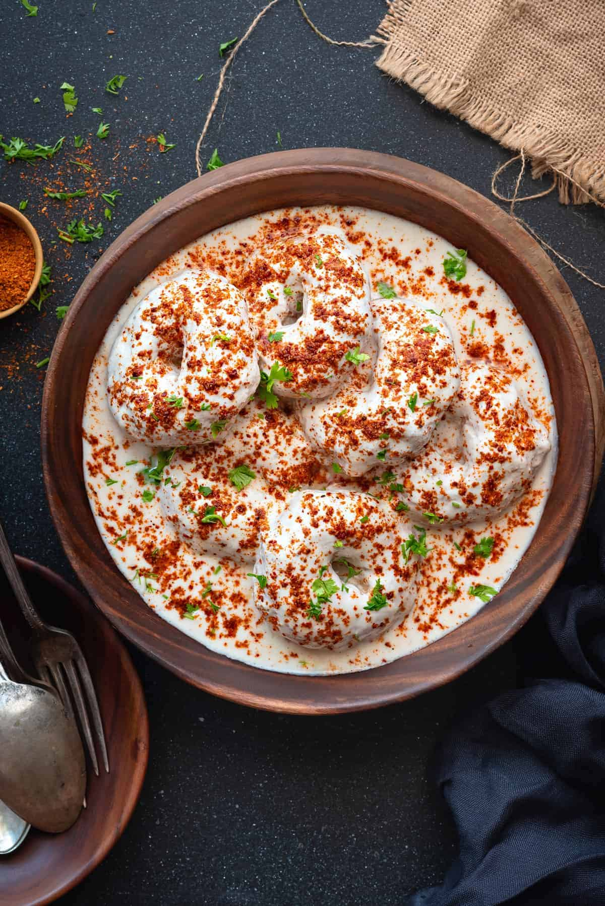 Close up shot of soft Dahi Vada served in wooden bowl.