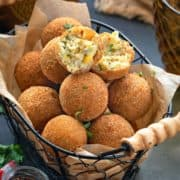 Corn cheese balls served in basket with one ball cut open showing the texture inside.