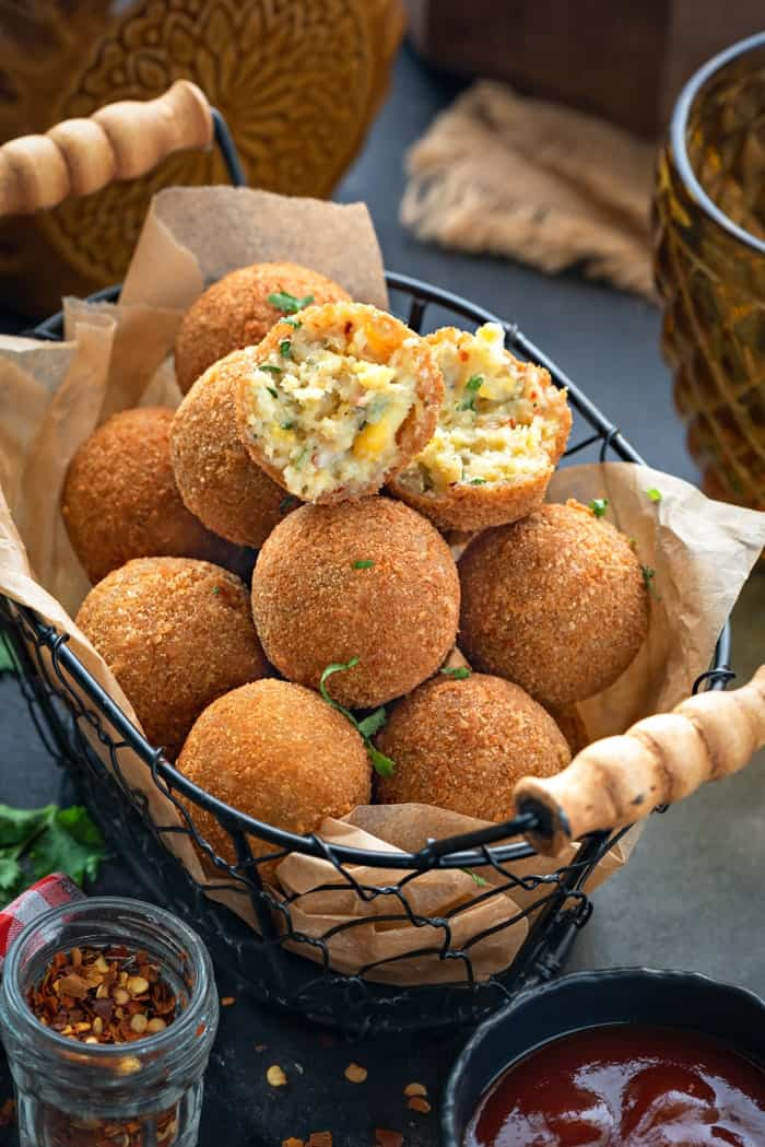 Corn cheese balls served in basket with once ball cut open showing the texture inside.