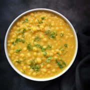 Delicious Ragda or white peas curry served in white bowl, black cotton linen at the side.