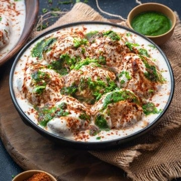 Soft fluffy Dahi Vada topped with green chutney and sweet chutney served in black plate.