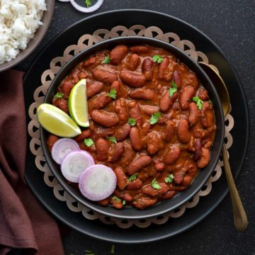 Punjabi Rajma masala curry served in black plate with a spoon into it.