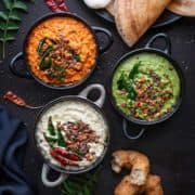 Red, white and green coconut chutney in 3 different black bowls.