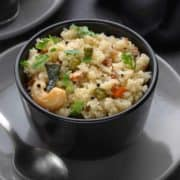 Rava Upma served in small black bowl with spoon along side.