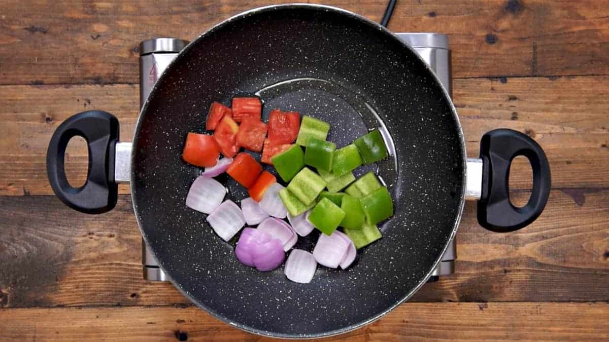 Onion, capsicum and tomato cubes added in hot oil in pan.