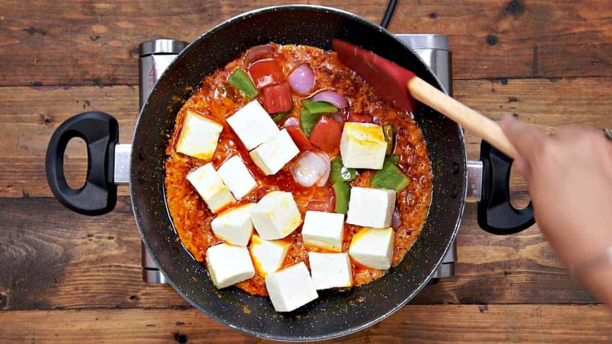 Paneer, roasted onion, tomato and capsicum added in pan.