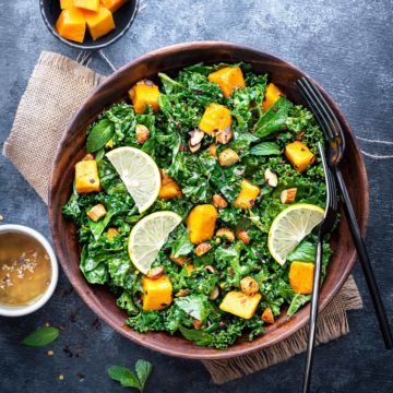 Mango Kale Salad in wooden bowl with 2 forks in it, cut mangoes and dressing in two small bowls on side.
