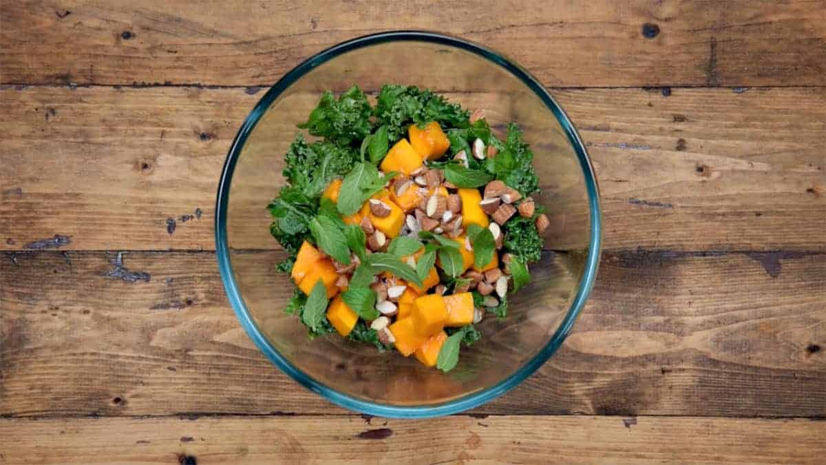 Mango cubes, almonds, fresh mint leaves, salt and pepper added to softened Kale.