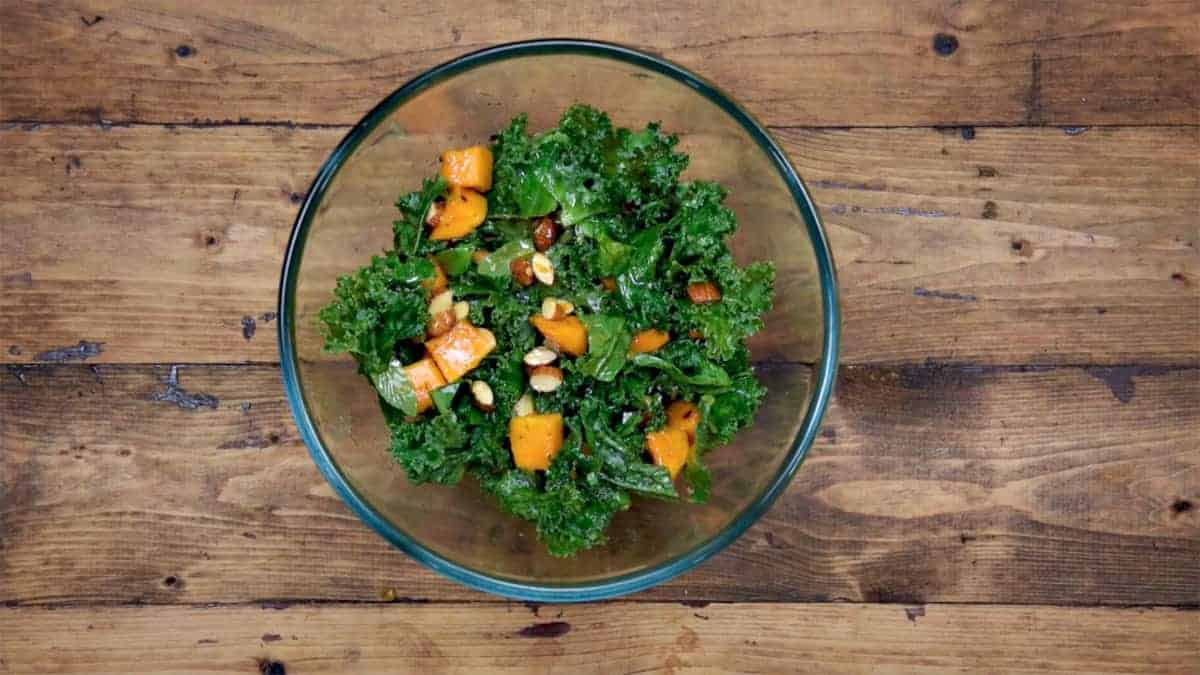 Mango Kale Salad with almonds and lemon dressing is ready to serve.