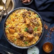 Overhead shot of Bombay Mutton Biryani served in large black bowl with raita on the side.