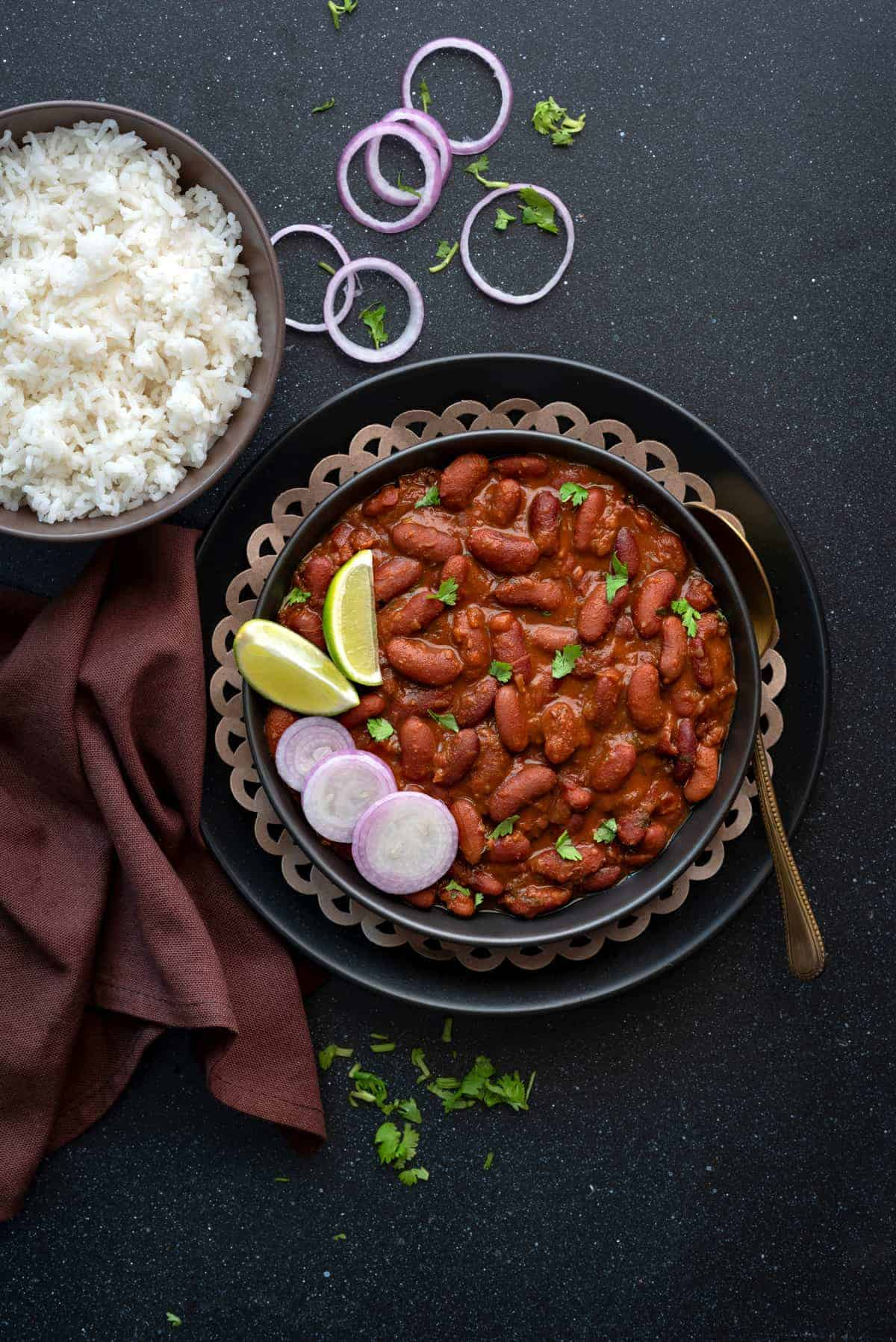 Red kidney beans curry on black plate with a spoon into it, bowl of rice on the side.