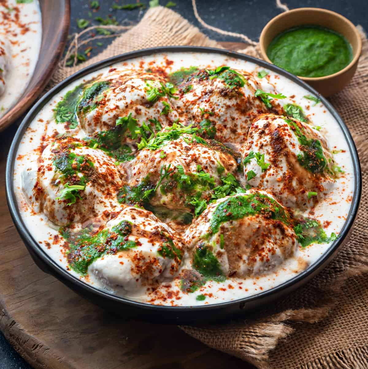 Dahi Vada topped with sweet and spicy chutney and served in black plate, green chutney at the back.
