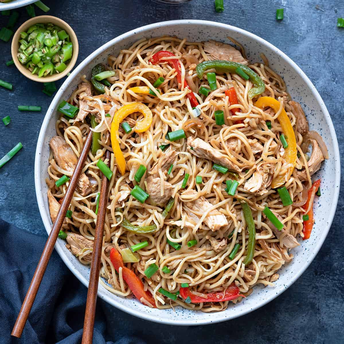 Chicken Hakka Noodles in blue bowl with pair of chopsticks into it.