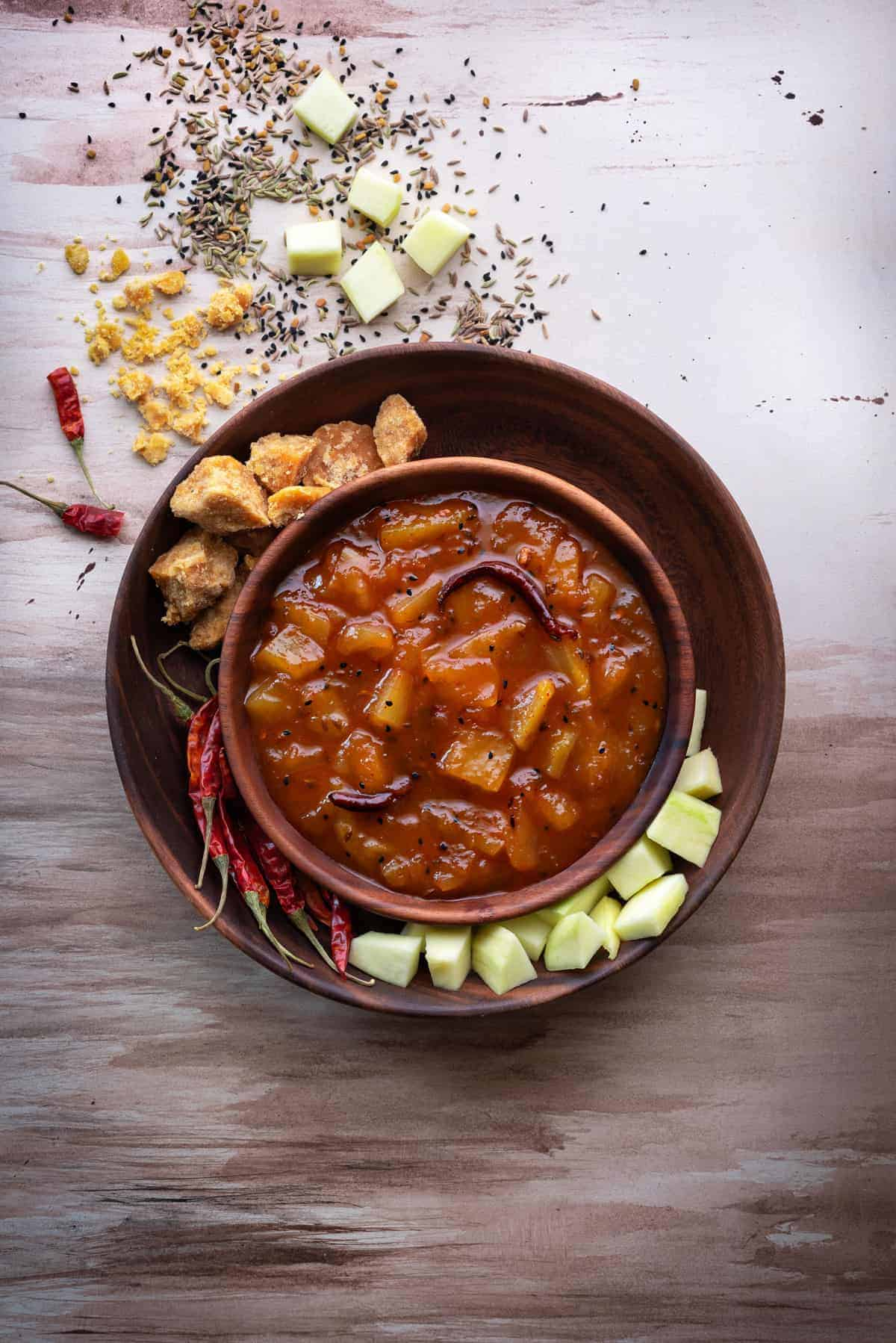 Sweet raw mango chutney in wooden bowl with jaggery, mango and red chillies spread around.