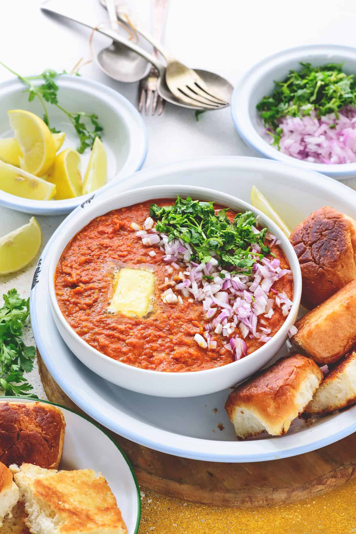 Garnished Pav Bhaaji served in white bowl with buttered buns, chopped onions and lemon wedges.