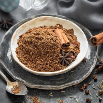 Chinese five spice powder in small ceramic plate, some whole spices spread around.