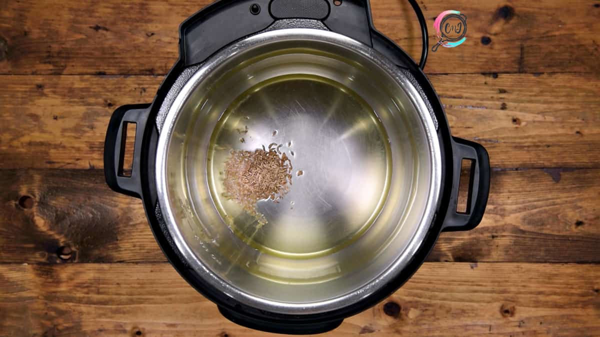 Cumin seeds added in hot in steel pot of Instant Pot.