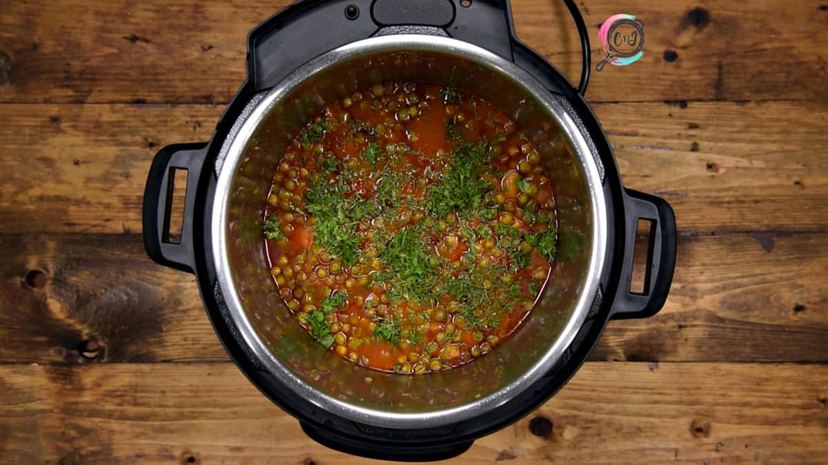 Chopped cilantro and dill added to the cooked aloo matar curry in the pot.