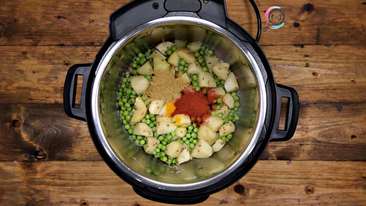 Turmeric, coriander powder and red chilli powder added to sautéed peas and potato in pot.