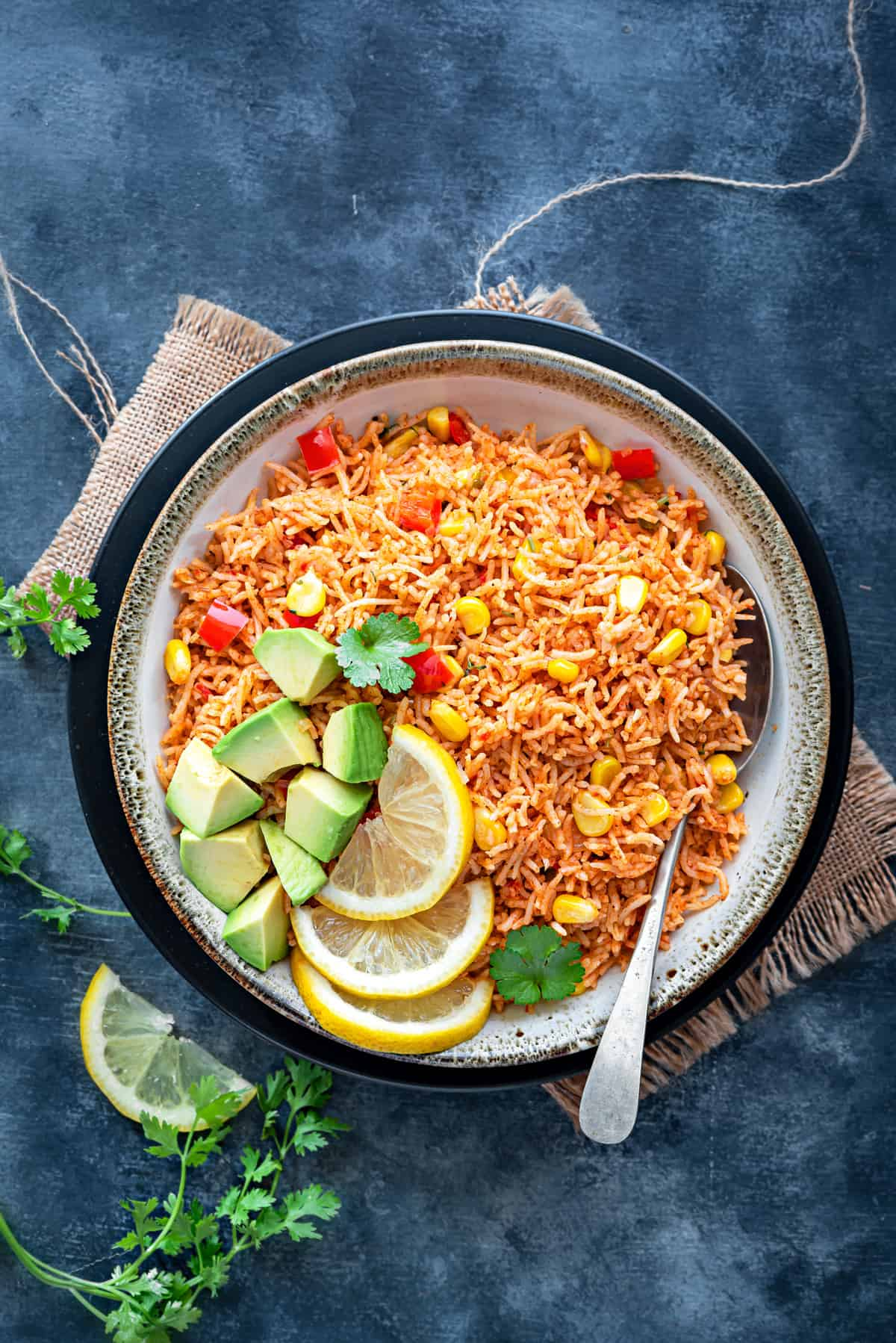 Top shot of garnished Spanish Rice Arroz Rojo in grey bowl with spoon.