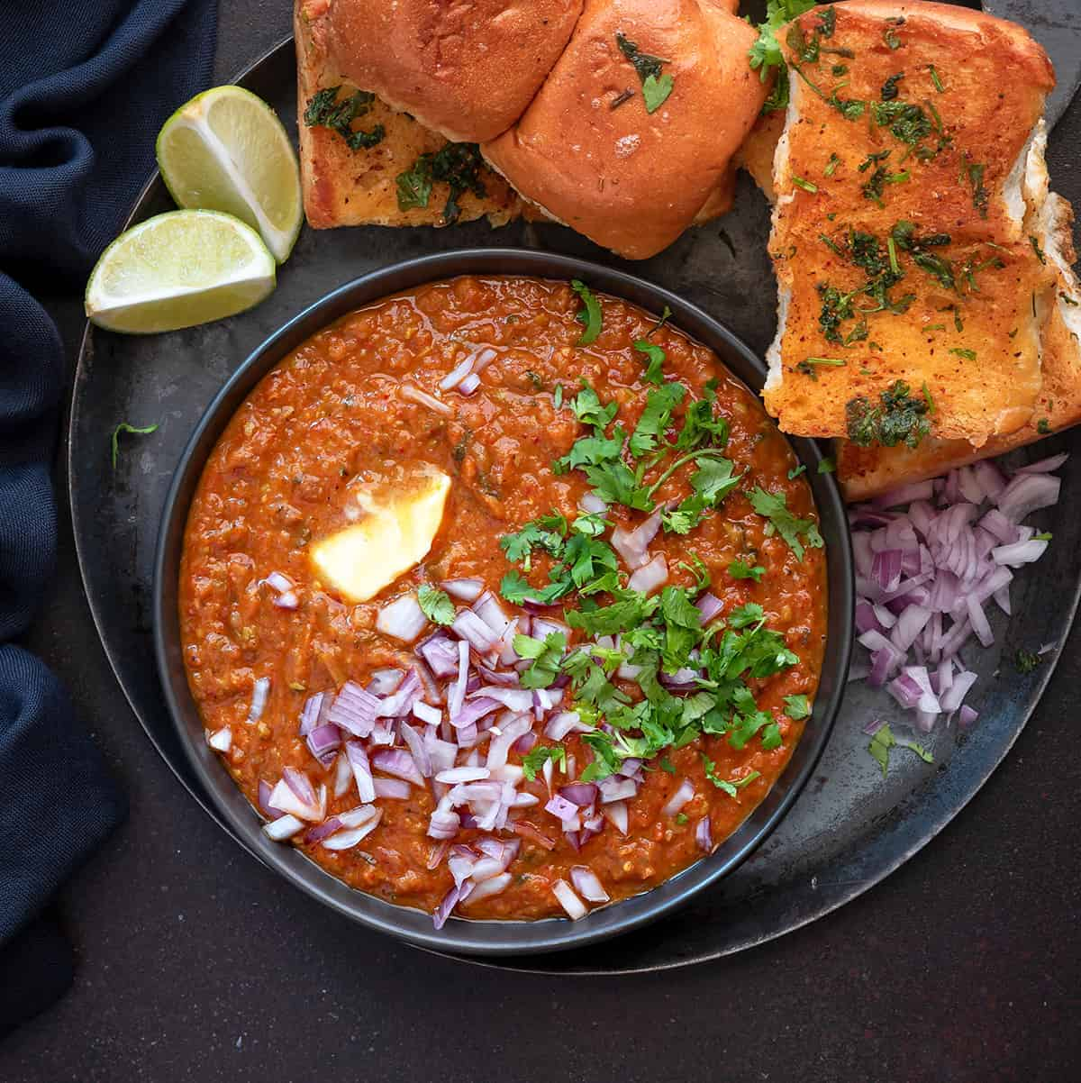 Mumbai Pav bhaji served in black plate with toasted buns, lemon wedges and chopped onions.