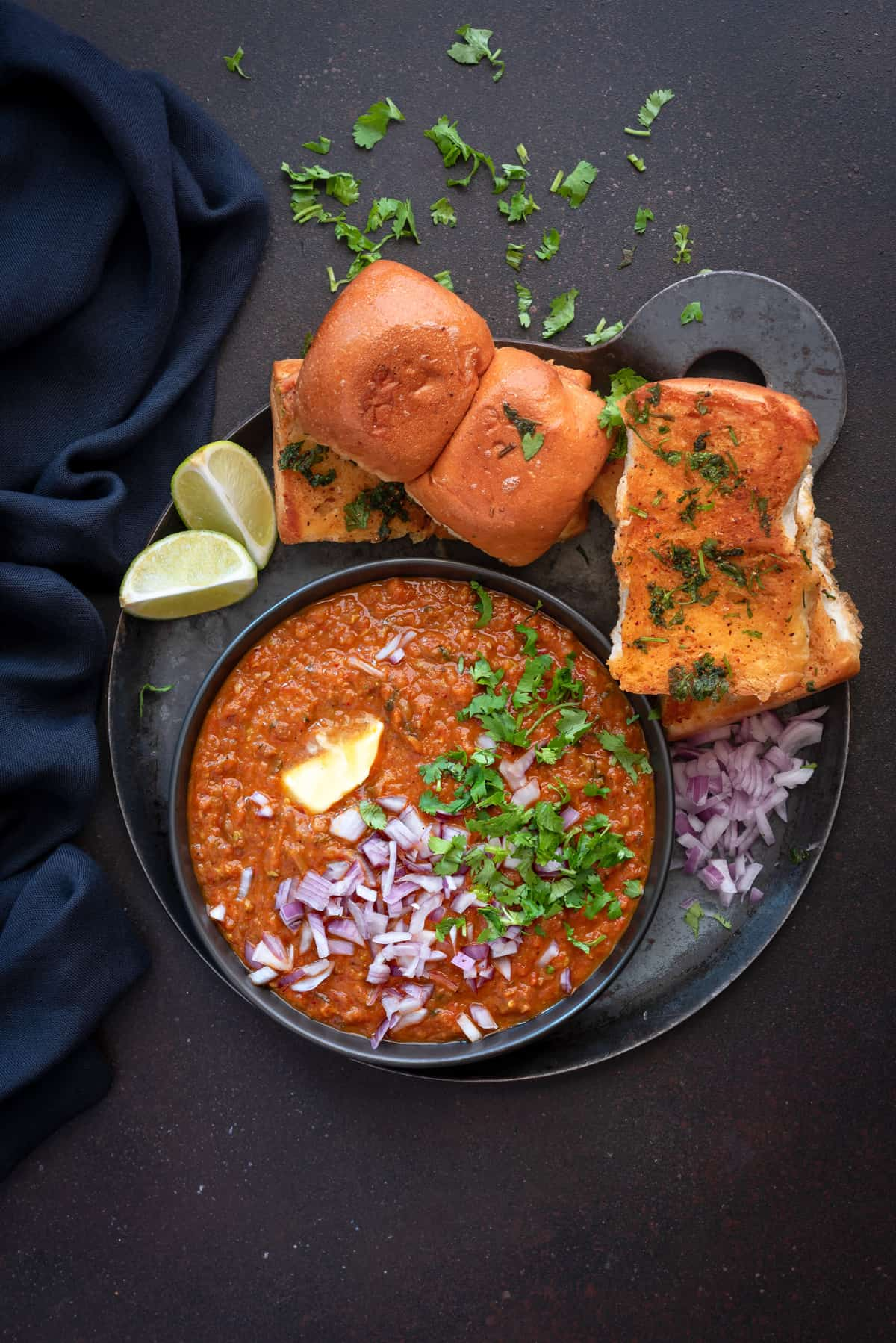 Pav bhaji served in black plate with toasted pav, lemon wedges and chopped onions.