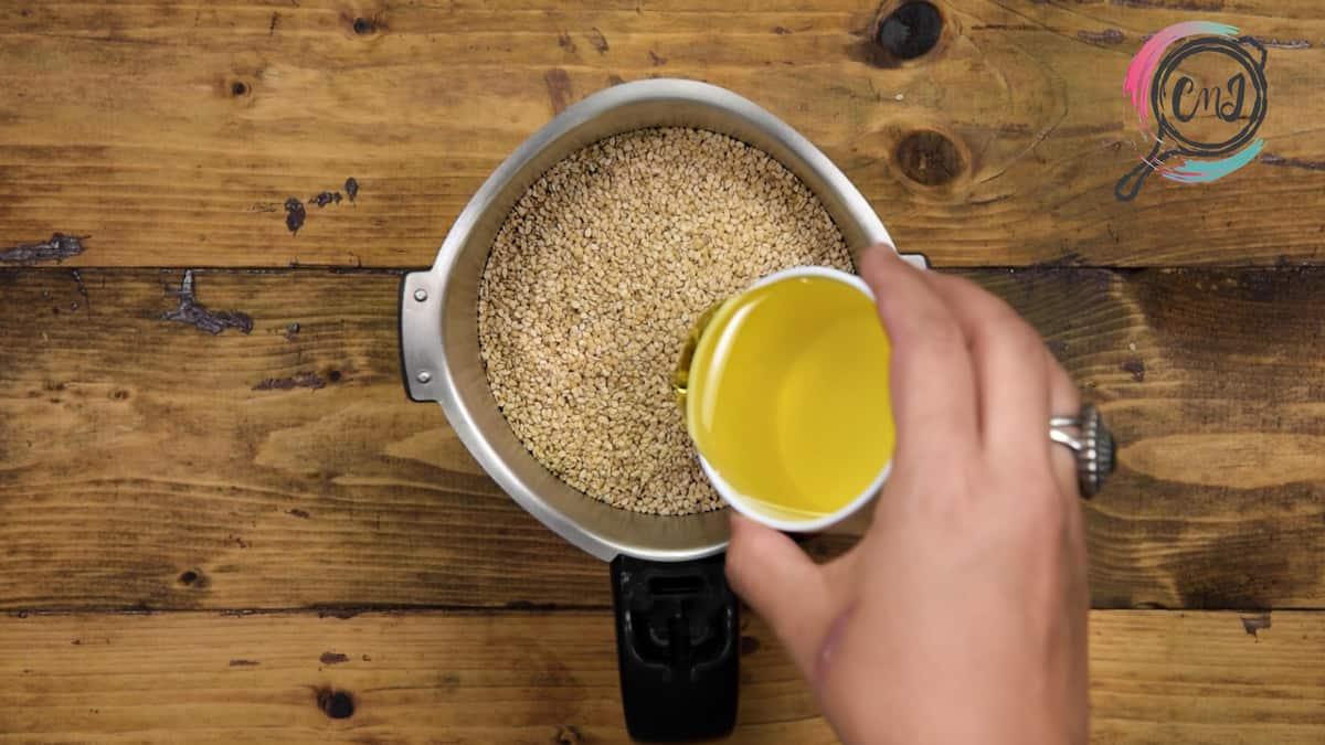 Adding olive oil into the blender jar.