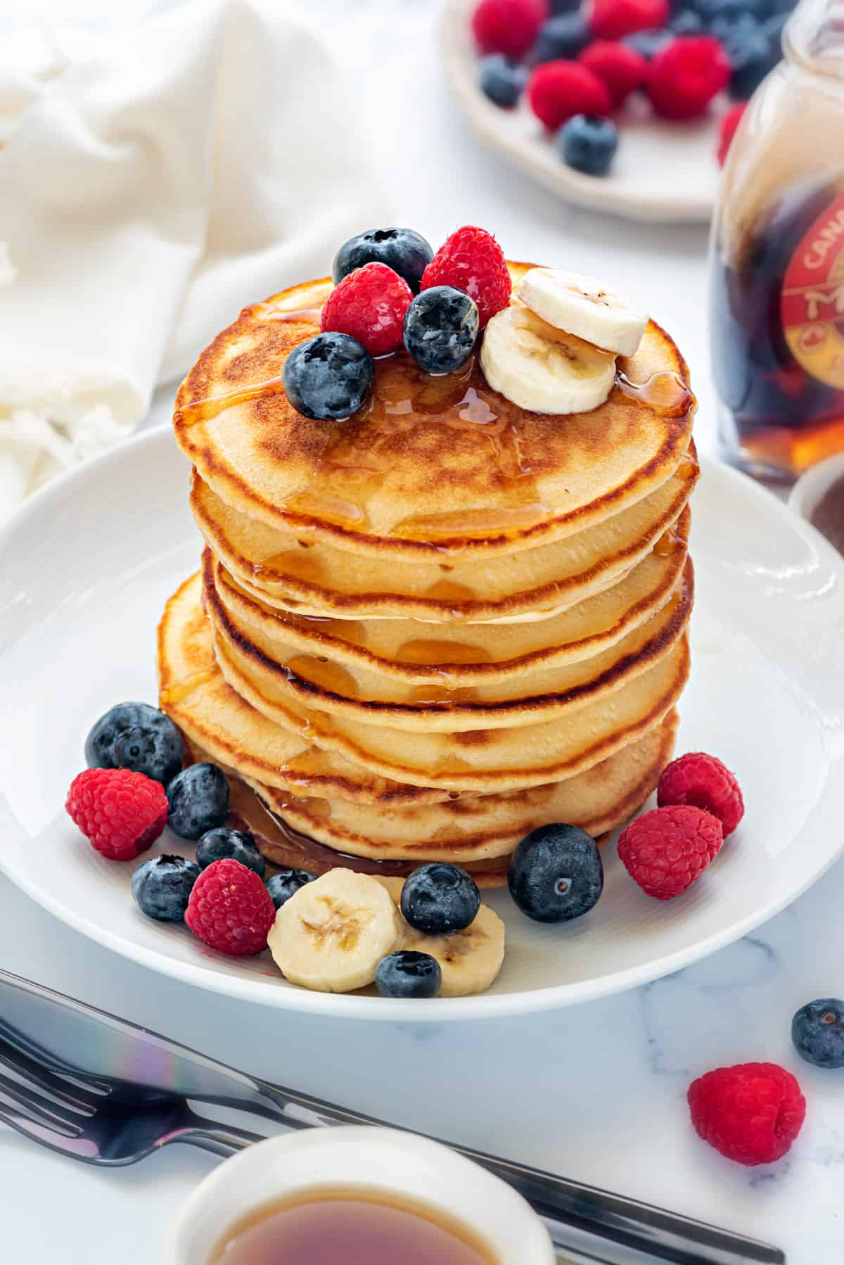 Stacked pancakes topped with maple syrup in white plate with berries, fork and knife on side.