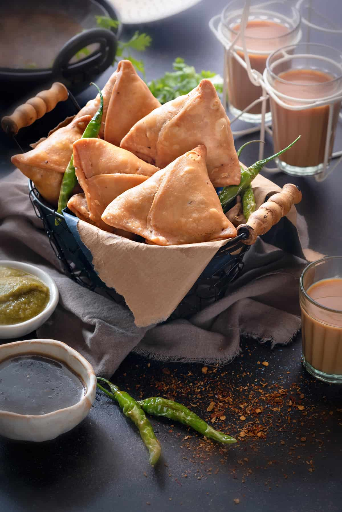 Punjabi samosas in basket, with sweet and spicy chutney, fried chilies and tea on the side.