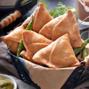 Indian Punjabi samosas in basket, with sweet and spicy chutney, fried chilies and tea on side.